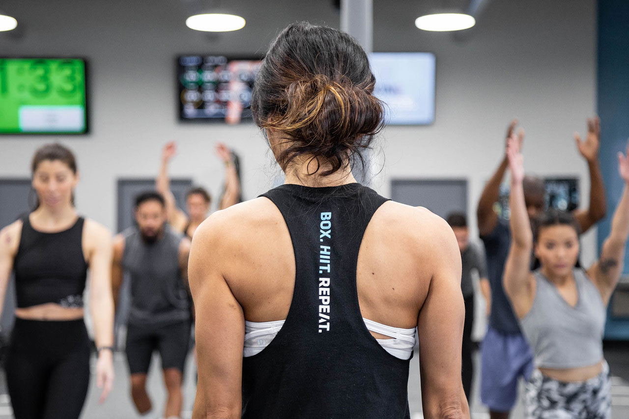 Back shot of coach facing members for a class