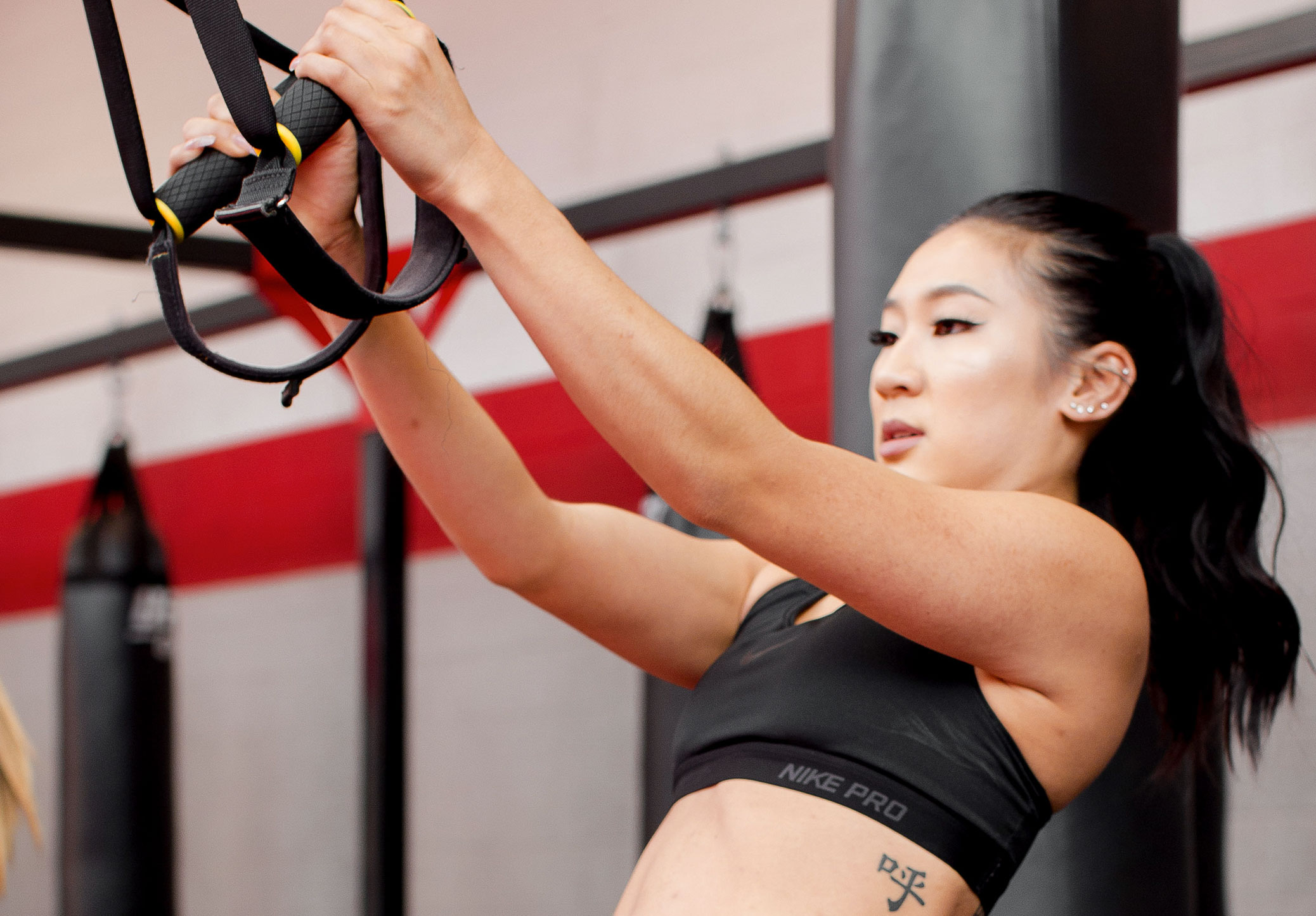 Member pulling herself with resistance band to practice for mma class